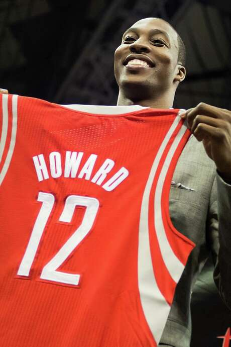 Dwight Howard holds up his new jersey as he is introduced as the newest member of the Houston Rockets during ceremonies at Toyota Center on Saturday, July 13, 2013, in Houston. The free agent officially joined the Rockets on Saturday with a news conference and public rally. ( Smiley N. Pool / Houston Chronicle ) Photo: Smiley N. Pool, Staff / © 2013  Houston Chronicle