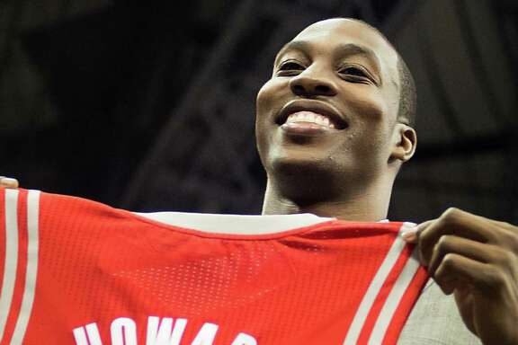 Dwight Howard holds up his new jersey as he is introduced as the newest member of the Houston Rockets during ceremonies at Toyota Center on Saturday, July 13, 2013, in Houston. The free agent officially joined the Rockets on Saturday with a news conference and public rally. ( Smiley N. Pool / Houston Chronicle )