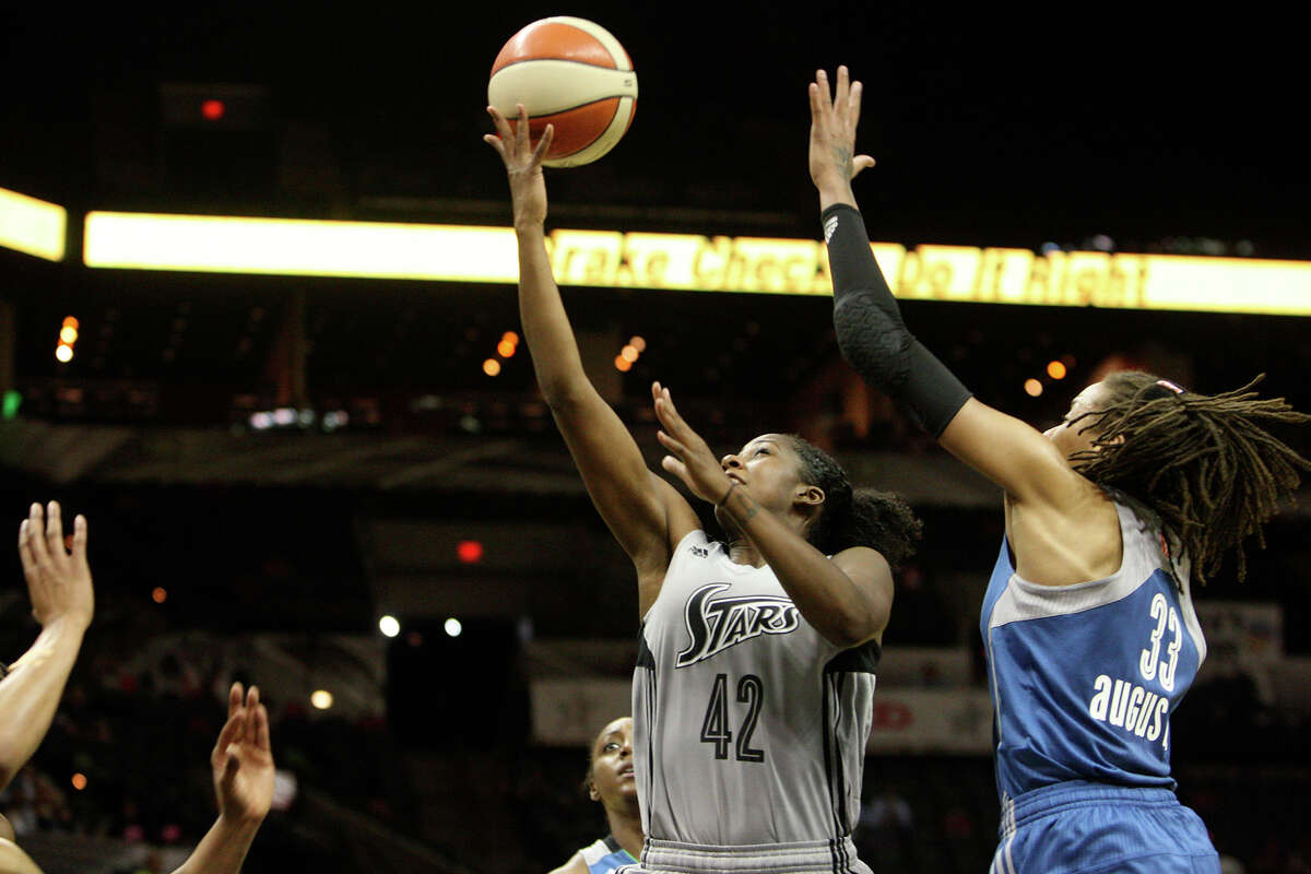 Shenise Johnson (42) shoots a layup past Selmone Augustus (33) at the game between the Silver Stars and the Minnesota Lynx at the AT&T Center on Tuesday, Aug. 6, 2013. The Lynx beat the Silver Stars, 80-93.