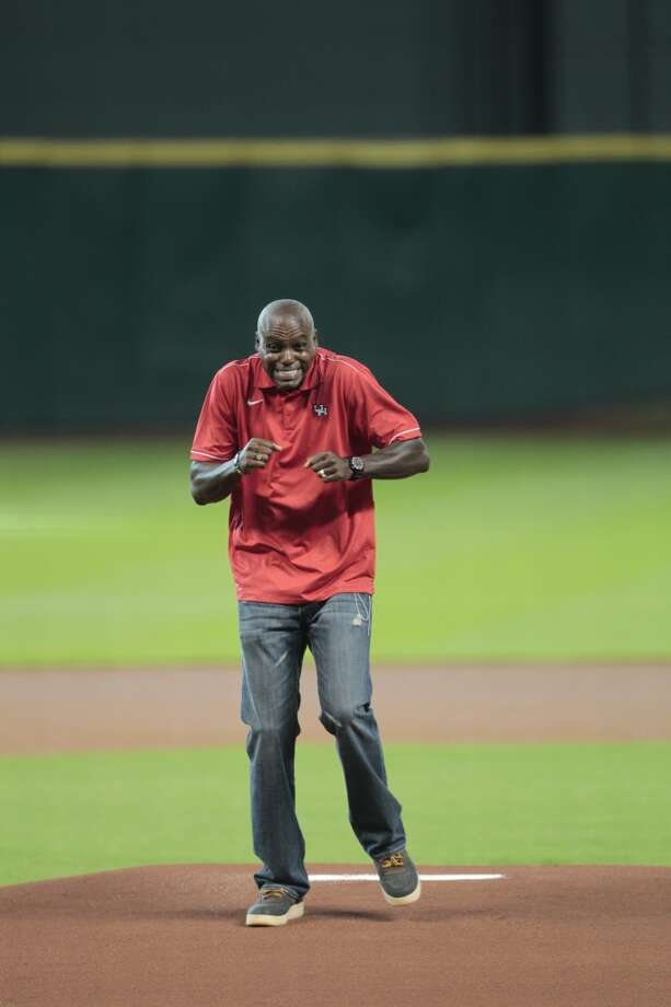 Olympic gold medalist and former UH athlete Carl Lewis  reacts after throwing a wild ceremonial first pitch. Photo: Billy Smith II, Houston Chronicle