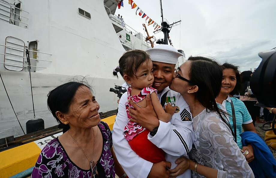 A Philippine sailor (C) from the BRP Ramon Alcaraz, a high-endurance Hamilton-class cutter that had been decomissioned by the US Coast Guard and acquired by Manila, is welcomed by his family shortly after the ship's arrival at the former US naval base in Subic Bay, Zambales province, northwest of Manila on August 6, 2013.  The Philippines vowed intensified sea patrols on August 6 as it welcomed the arrival of its latest war ship from ally the United States amid a maritime row with China.    AFP PHOTO / TED ALJIBETED ALJIBE/AFP/Getty Images Photo: Ted Aljibe, AFP/Getty Images