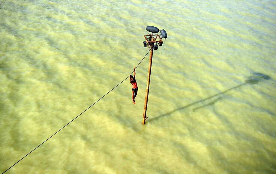 A teenager dangles from a power line before diving into floodwaters of the overflowing Ganges River in Allahabad India. Monsoon rains have caused the Ganges to surge over its banks. Photo: Sanjay Kanojia, AFP/Getty Images