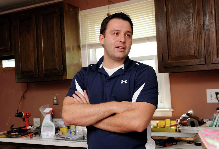 George Psarofagis, 27, who recently bought his first home on Mountainville Avenue in Danbury, Conn., stands  in the kitchen, which like the rest of the house is undergoing extensive renovations, Tuesday, August 6, 2013. Photo: Carol Kaliff / The News-Times