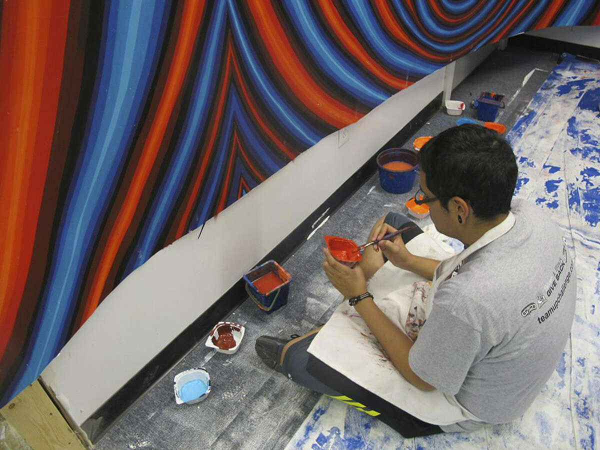 A student works on a San Anto Cultural Arts mural titled