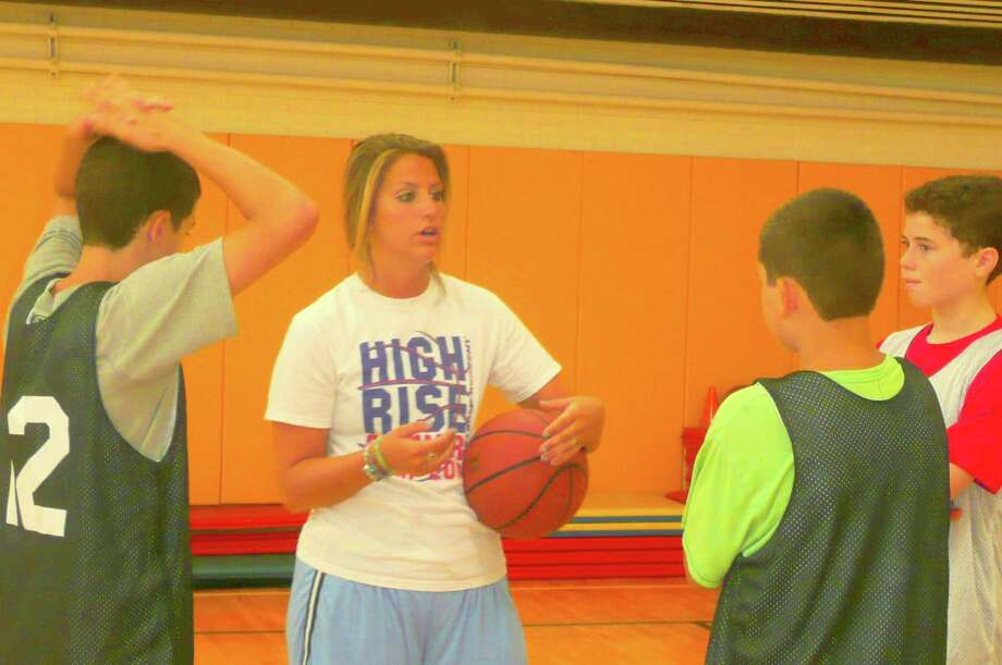 """Former Greenwich High School and Wheaton College hoop star Jana Jagodzinski wants to keep her hand in the game she loves so she worked this summer coaching at the High Rise Academy basketball camp, which was held at Eagle Hill School. """"I absolutely love coaching the kids at High Rise Basketball Camp,"""" she says. Here she shares some tips with campers. Photo: Anne W. Semmes"""
