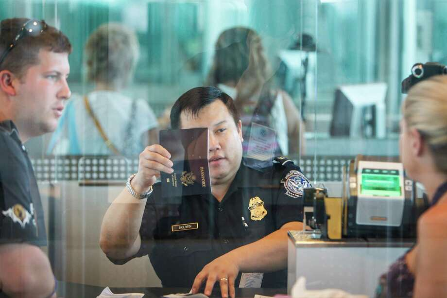U.S. Customs and Border Protection officer Nguyen looks at a passport at the Federal Inspection Services customs facility at Bush Intercontinental Airport in Terminals E, Wednesday, May 23, 2012, in Houston. Photo: Michael Paulsen, Houston Chronicle / © 2012 Houston Chronicle