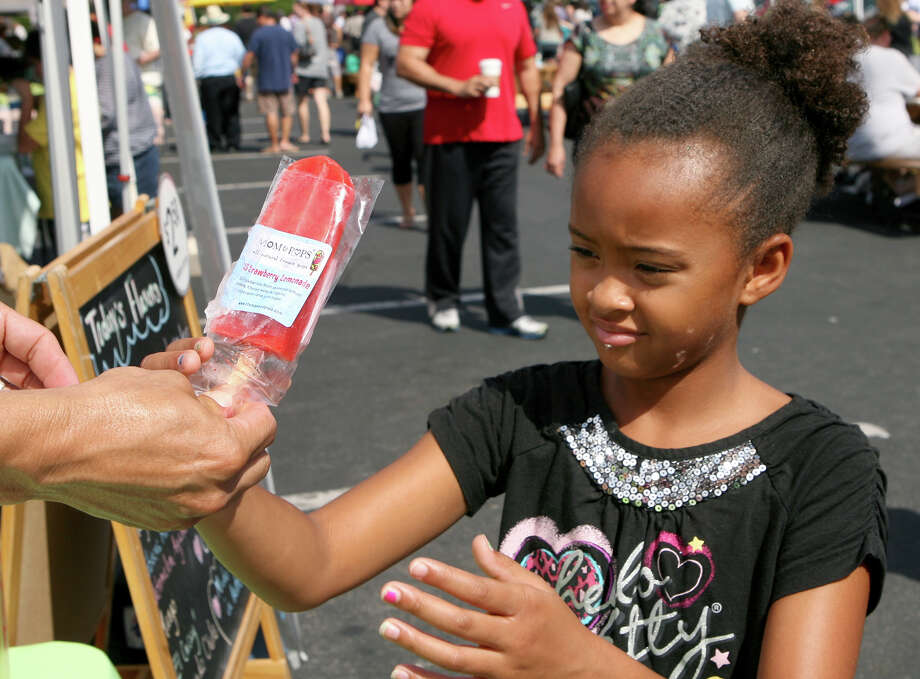 Nia Webber, 9, takes a strawberry lemonade paleta from Mom & Pops all natural pops booth Sunday, July 14, 2013 at the Quarry Farmers & Ranchers Market. The business is based in Austin but is sold every Sunday at the Farmers and Ranchers Market. Photo: Cynthia Esparza, For San Antonio Express-News / For San Antonio Express-News