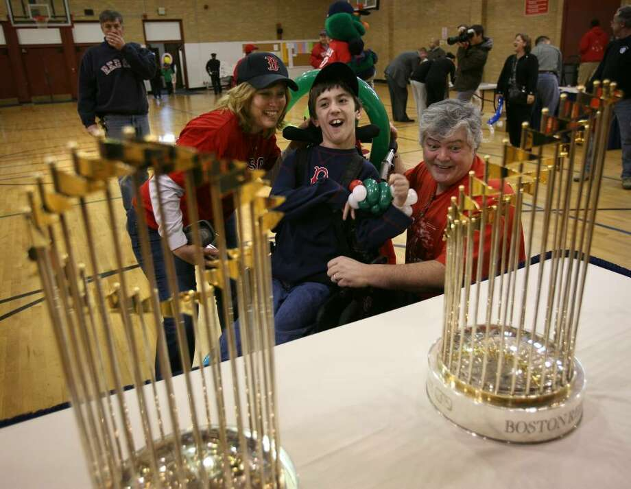 Jesse Ebstein, 11 of Milford, who has cerebral palsy, and his parents, Dawn and Mike Dickinson, were among the first to glimpse the two Red Sox world championship trophies on display at the Parsons Complex gymnasium in Milford on Wednesday, January 20, 2010. Photo: Brian A. Pounds / Connecticut Post