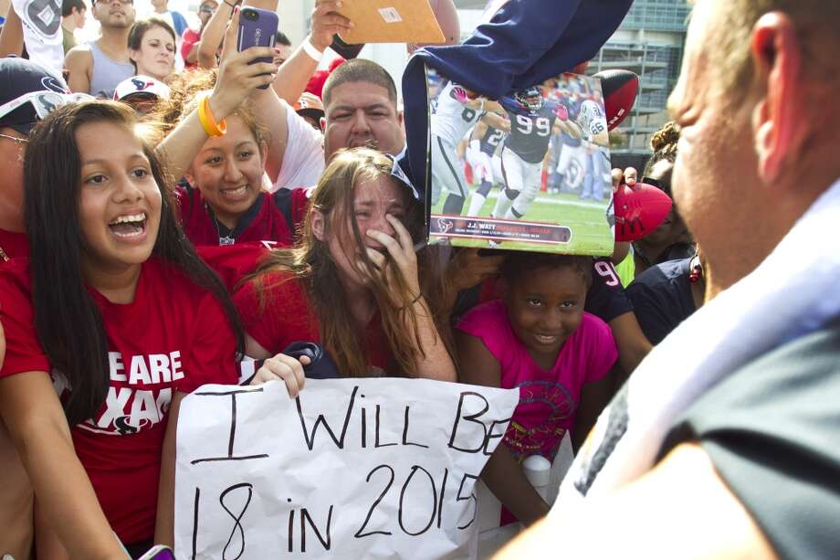Fan Katie Kaulfold, center, reacts as she meets J.J. Watt at training camp on Wednesday. Photo: Brett Coomer, Chronicle