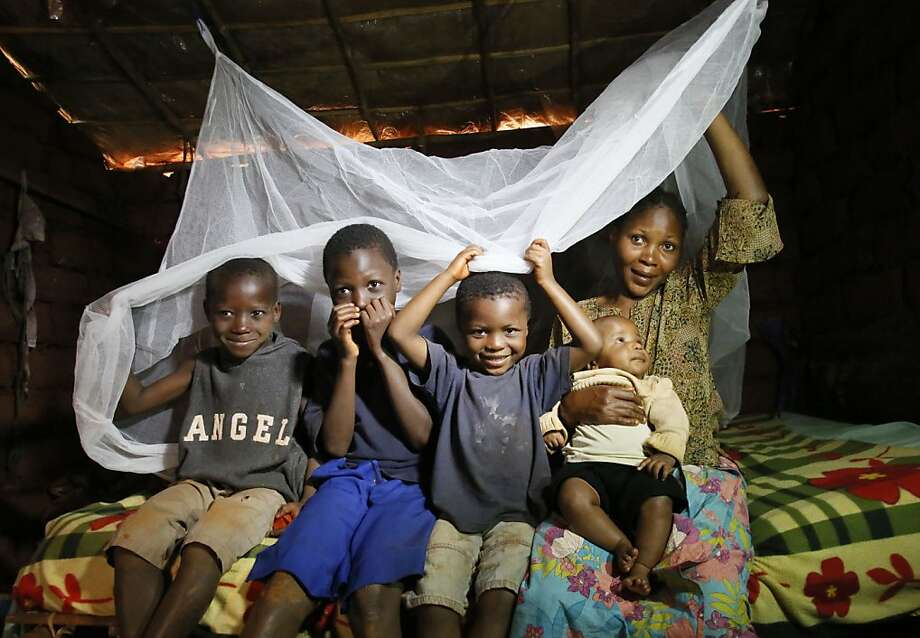 A family displays its mosquito net in the Nyarugusu refugee camp in Tanzania, where Golden State Warriors guard Stephen Curry went to help. Photo: Stuart Ramson, UN Foundation