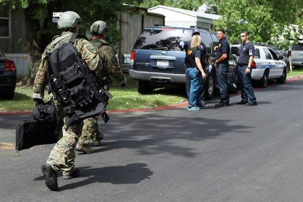 SWAT team members arrive at the scene of a shooting at a mobile home park at 660 Maxey Road, Wednesday, Aug. 7, 2013, in Houston. A woman was shot and transferred to LBJ hospital, the suspect shot at officers who responded to the scene, and then barricaded himself inside his residence. SWAT was called but he was quickly arrested.