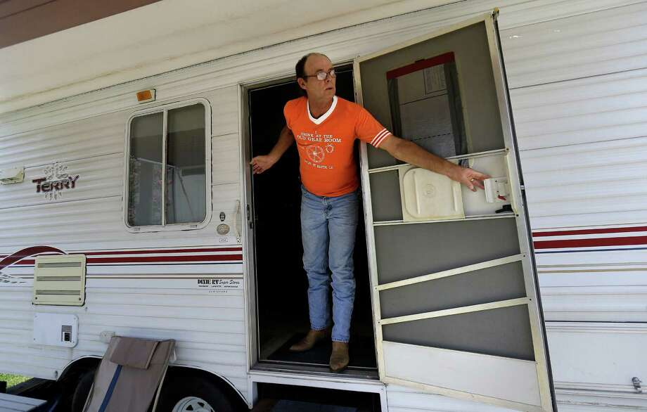 In this Thursday, June 27, 2013 photo, Kenny Simoneaux looks out the door of the camper he is living in, in a campground in Pierre Part, La., after being displaced by the mandatory evacuation from the approximate 22-acre sinkhole in Bayou Corne. Neighbors in tiny Bayou Corne face a wrenching decision after a huge sinkhole opened up near their community: Do they stay put or should they pack up and move? The sinkhole resulted from a collapsed underground salt dome cavern about 40 miles south of Baton Rouge. After oil and natural gas came oozing up and acres of swampland liquefied into muck, the community's 350 residents were advised to evacuate. Texas Brine Co., the operator of the salt dome, is negotiating buyouts of residents who have not joined lawsuits against the company. (AP Photo/Gerald Herbert) Photo: Gerald Herbert, STF / AP