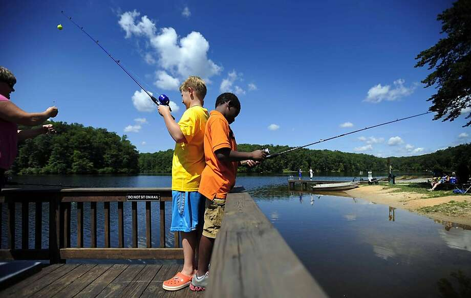 Shall we say spinning rods at noon? Eli Heaney and Salih Singhj duel for freshwater fish at Mott's Run in Spotsylvania County, Va. Photo: Reza A. Marvashti, Associated Press