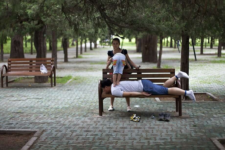 Keep dancing, dear. Daddy has a knot in his deltoid: A mother holds her son so he can massage his father's back with his feet on a park bench in Beijing. Photo: Alexander F. Yuan, Associated Press
