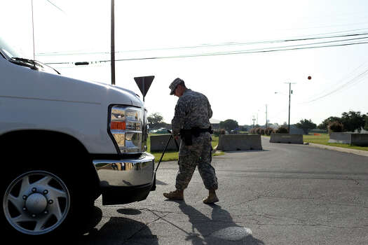 A soldier checks the undercarriage of a vehicle at a security checkpoint outside the Lawrence H. Williams Judicial Center on the second day of the trial for Maj. Nidal Hasan at Fort Hood in Killeen on Wednesday, August 7, 2013. Photo: Lisa Krantz, San Antonio Express-News / San Antonio Express-News