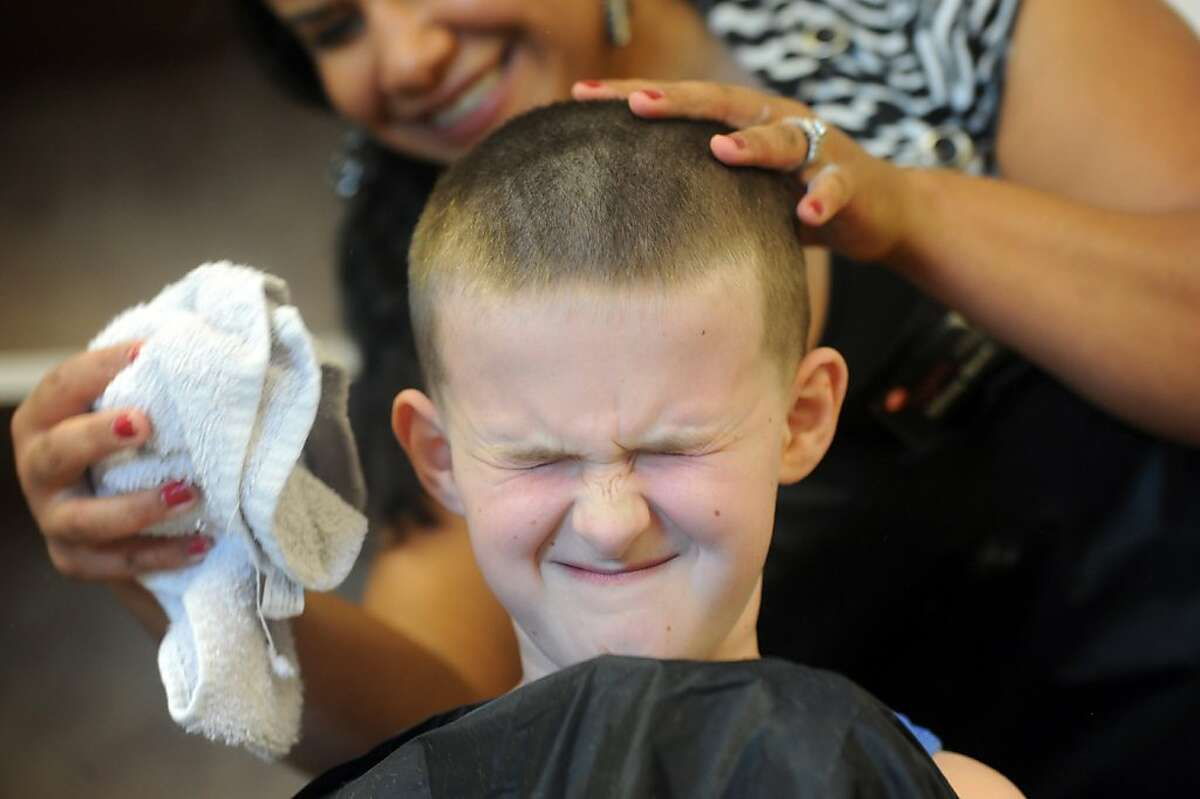 Just a little off the top, please: Tiffany Boren brushes away loose hair after giving 10-year-old Steven Grabb a buzz cut at Cedar Hall Community School's Health, Beauty and Fitness Day in Evansville, Ind. Roger's Hair Academy West donated stylists for the free back-to-school trims.