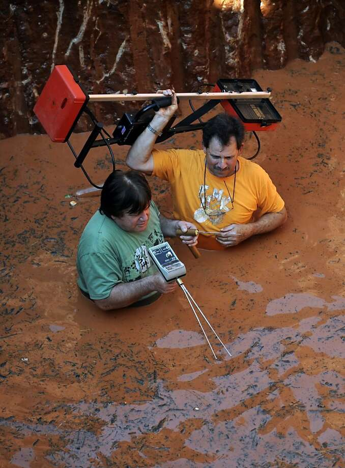 Thar's gold in them thar suburbs:Paraguayan treasure hunters use metal detectors in a flooded pit while digging for 10 tons of gold they believe are buried at this spot in Capiata, a suburb of Asuncion. The crew of about 20, equipped with heavy machinery and operating without a permit, reportedly made a mess at the site. Their leader, Alberto Diaz, said he has historical references suggesting the alleged trove belonged to Francisco Solano Lopez, a military hero who died in a 19th-century war that pitted Paraguay against Argentina, Brazil and Uruguay. Photo: Norberto Duarte, AFP/Getty Images