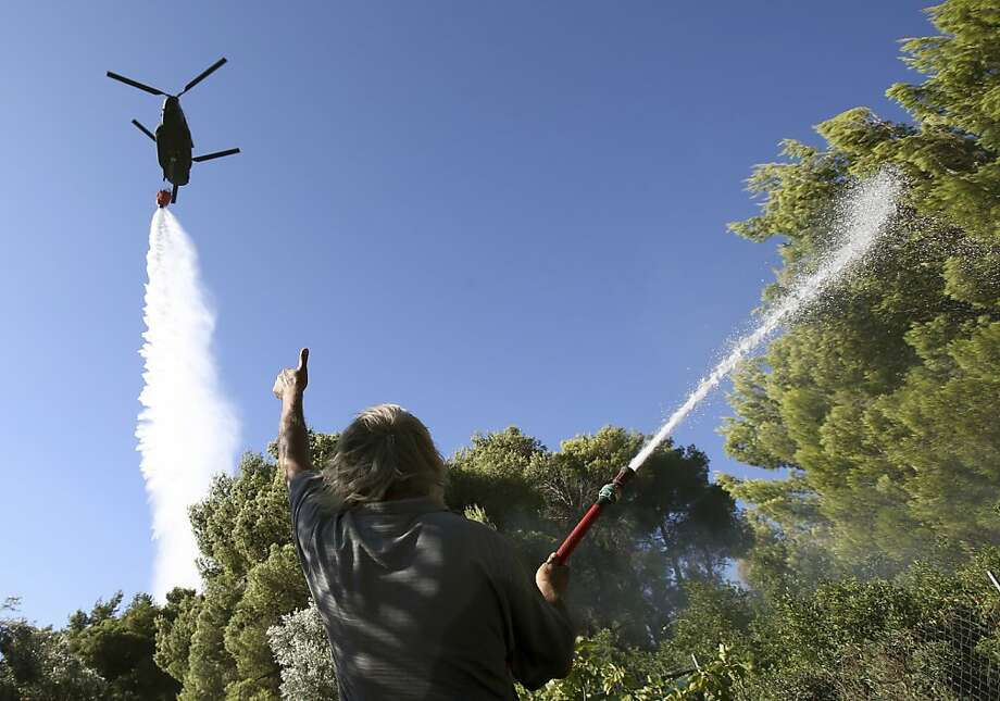 Bull's-eye! A resident of an Athenian suburb gives thumbs-up to a military helicopter dropping water over a burning forest. A large wildfire raged through the Varibobi suburb, destroying at least four homes. No injuries were reported. Photo: Thanassis Stavrakis, Associated Press