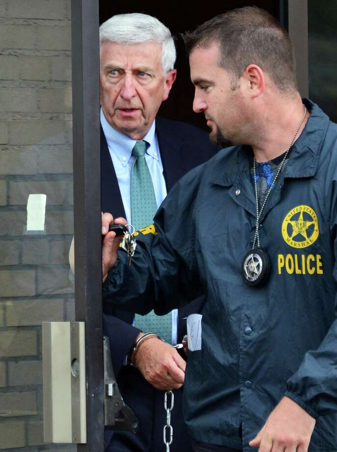 Former Albany broker David L. Smith, left, is lead in chains from U.S. District Court Wednesday, Aug. 7, 2013, in Utica, N.Y., after receiving a sentence of 10 years in federal prison. (John Carl D'Annibale / Times Union) Photo: John Carl D'Annibale / 00023444A