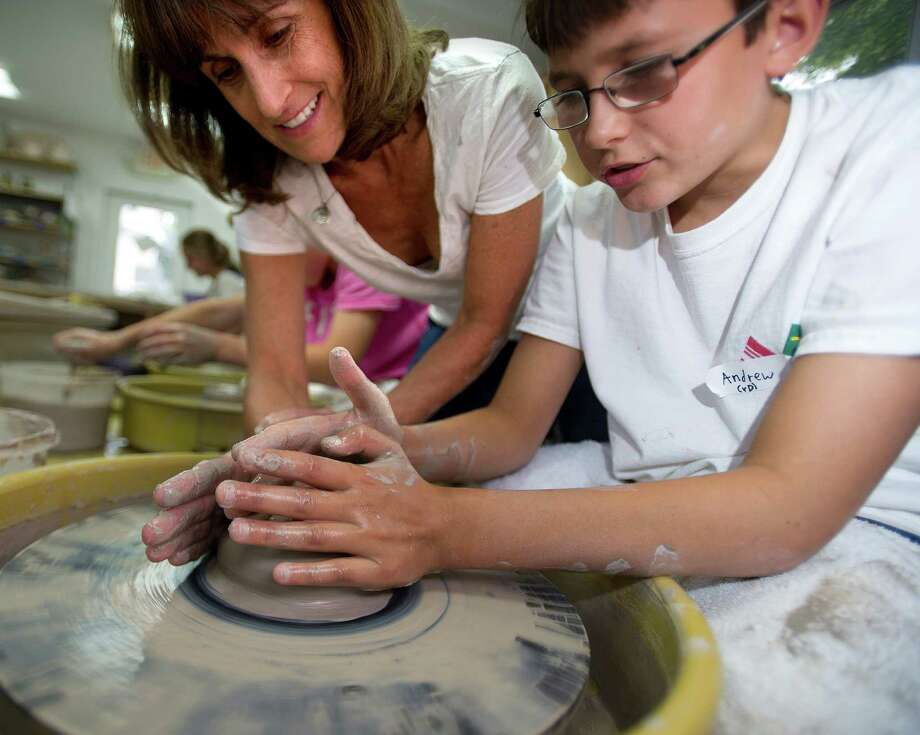 Lakeside Pottery co-owner Patty Storms helps Andrew Butcher, 12, make a mug during camp on Wednesday, August 7, 2013. Photo: Lindsay Perry / Stamford Advocate