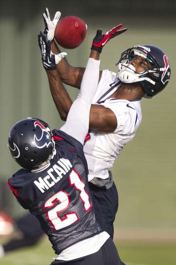 Wide receiver Lestar Jean (18) and cornerback Brice McCain (21) leap for a pass in the end zone.