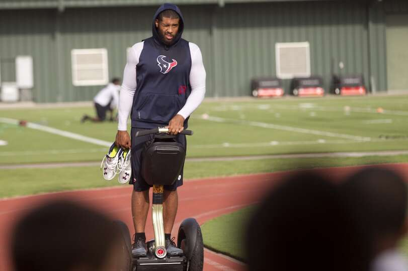 Running back Arian Foster rides across the practice facility on a Segway.