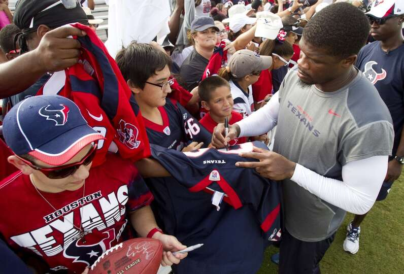 Wide receiver Andre Johnson signs autographs after practice.