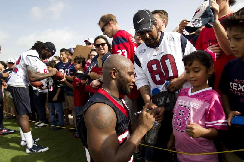 Free safety Danieal Manning, right, and wide receiver Keshawn Martin, far left, sign autographs afte