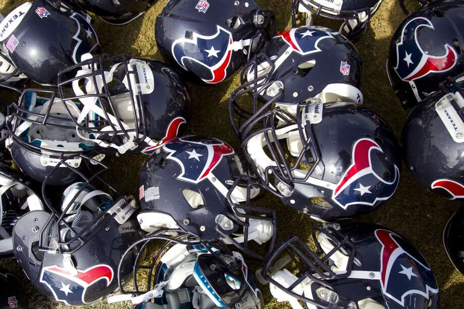 Texans helmets are stacked on the ground after practice. Photo: Brett Coomer, Chronicle