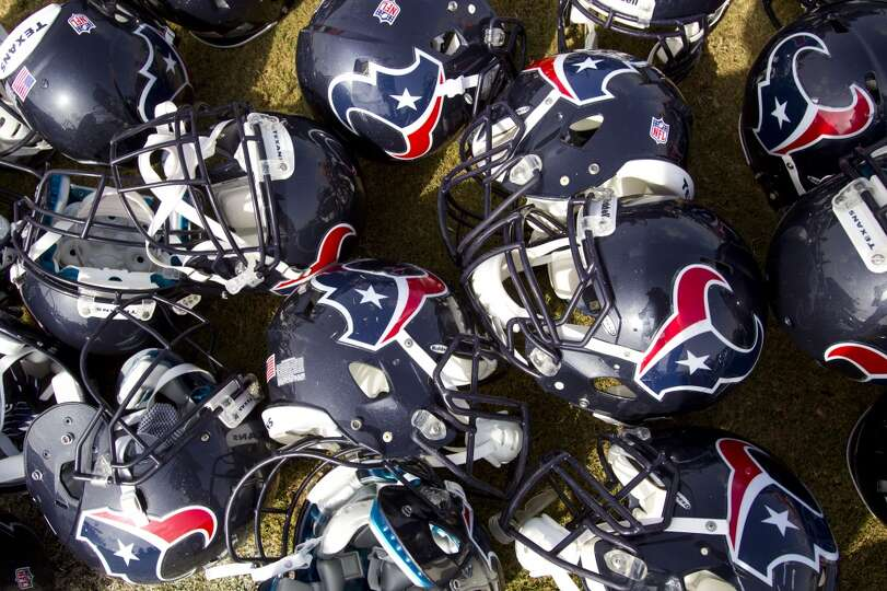 Texans helmets are stacked on the ground after practice.
