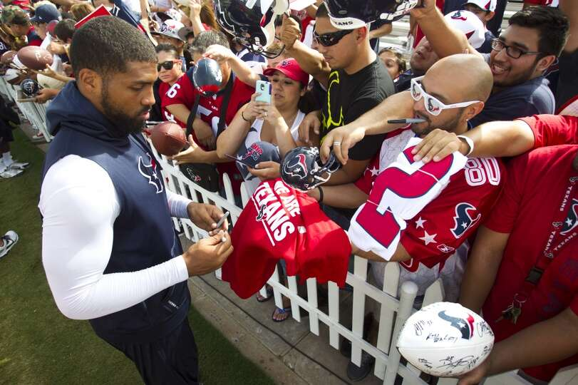 Running back Arian Foster, left, signs autographs after practice.