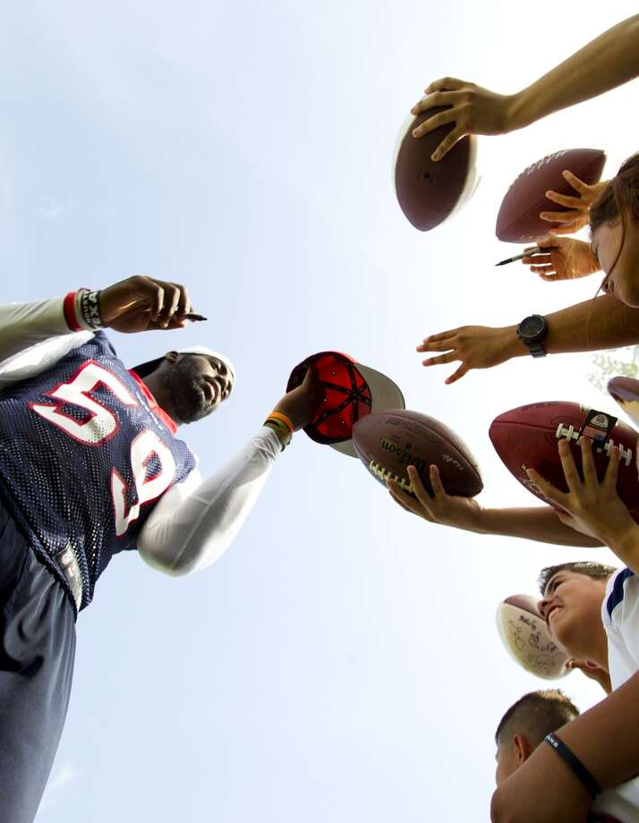 Outside linebacker Whitney Mercilus (59) signs autographs after practice. Photo: Brett Coomer, Chronicle