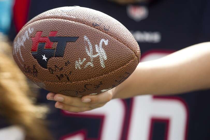 A fan holds out a football while seeking autographs.