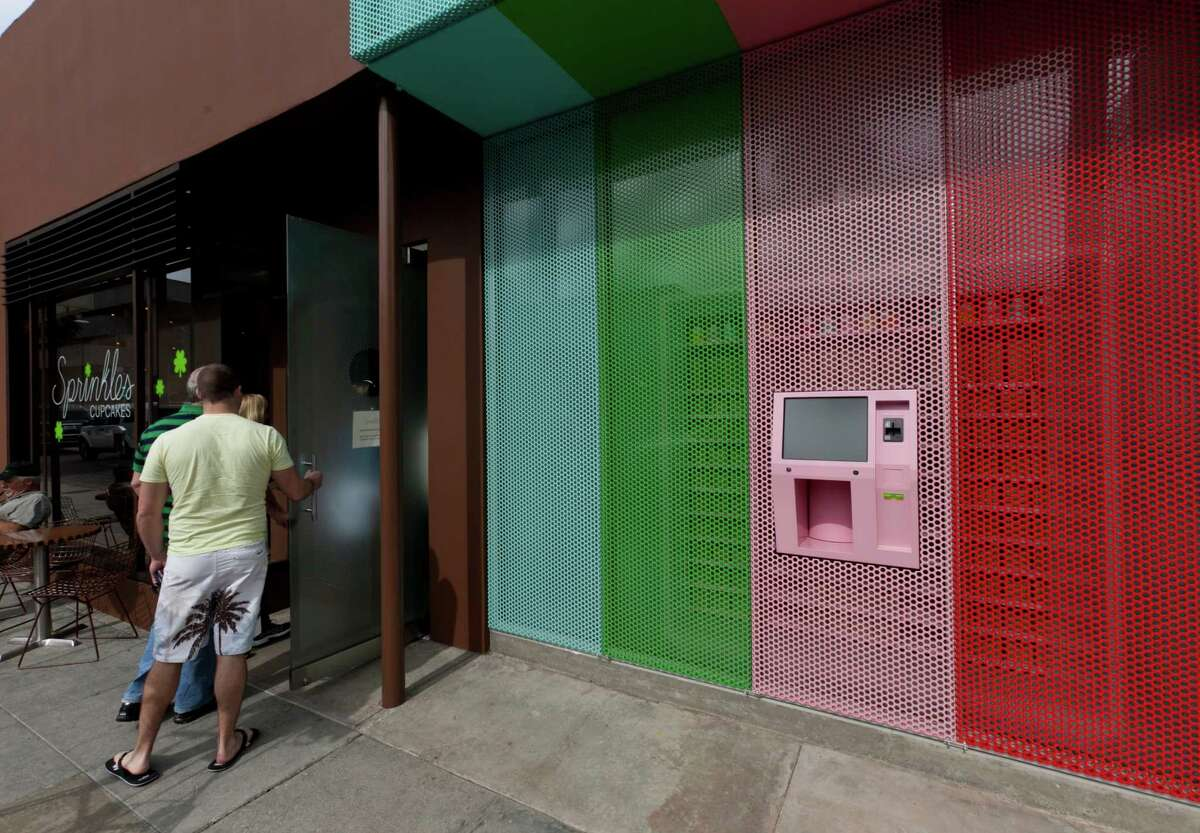 Sprinkles' first Cupcake ATM in Beverly Hills, seen in this March 5, 2012, photo, features a touchscreen and a robotic arm that pulls the correct flavor of cupcake from a wall of single-serving boxes inside the store. (AP Photo/Damian Dovarganes)