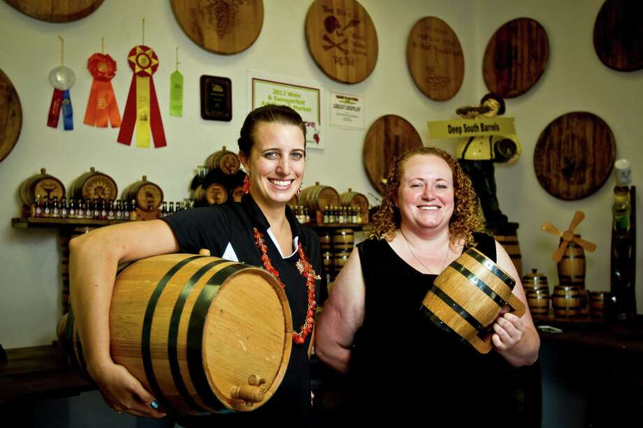 Deep South Barrels co-owner Elissa Emmons, left, and office manager Miranda Knerr show different sizes of custom barrels they can make, Tuesday, June 4, 2013, in Pearland . ( Nick de la Torre / Chronicle ) Photo: Nick De La Torre, Houston Chronicle / © 2013 Houston Chronicle