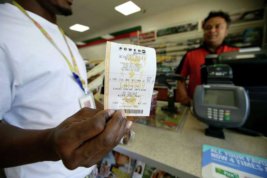 Raj Prasai, right, watches after making a sale to Eric, left, who did not want to give his last name in case he won the Powerball Jackpot, holds what he said would be the winning numbers after making the purchase, Wednesday, Aug. 7, 2013, in Dallas. The Powerball jackpot is expected to be about $425 million by Wednesday's drawing, making it the game's third largest ever. Photo: AP