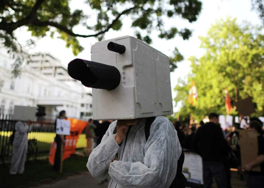 A demonstrator dressed as a surveillance camera joins a protest at the U.S. Consulate in Hamburg, Germany, to support Edward Snowden. A reader, however, agrees with a column that stated Snowden should accept the consequences of his actions. Photo: Angelika Warmuth, AFP / Getty Images