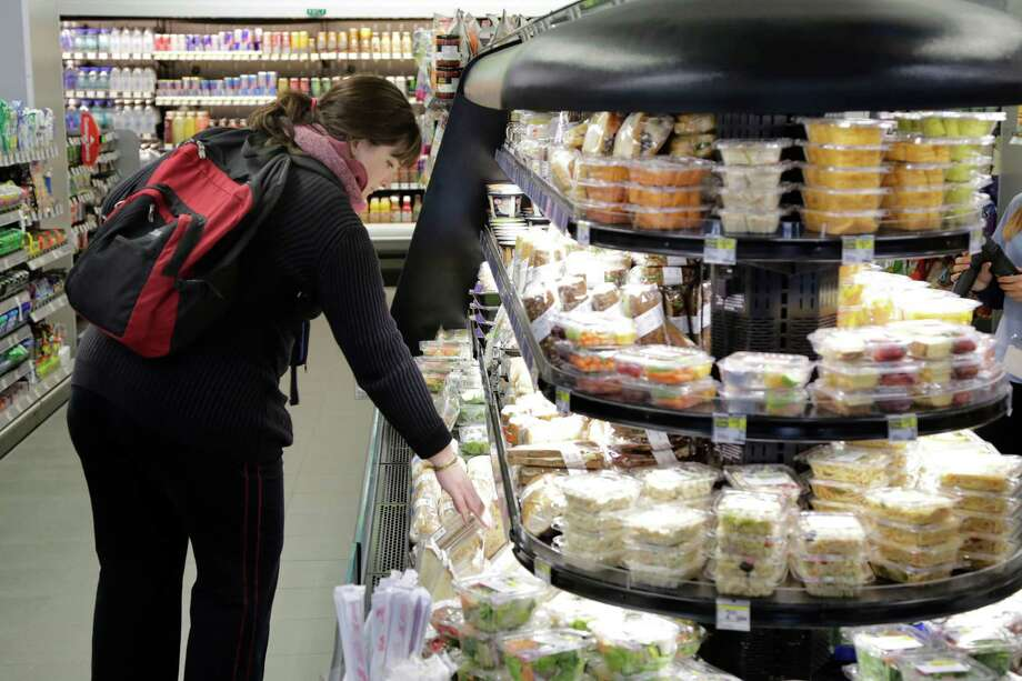 In this Wednesday, May 15, 2013, photo, a customer shops for a sandwich in the fresh food section at the Walgreens flagship store in the Empire State Building, in New York .The nation's major drugstore chains are opening more in-store clinics in response to the massive U.S. health care overhaul, which is expected to add about 25 million newly insured people who will need medical care and prescriptions, as well as  offering more services as a way to boost revenue in the face of competition from stores like Safeway and Wal-Mart.  (AP Photo/Mark Lennihan) ORG XMIT: NYBZ204 Photo: Mark Lennihan / AP