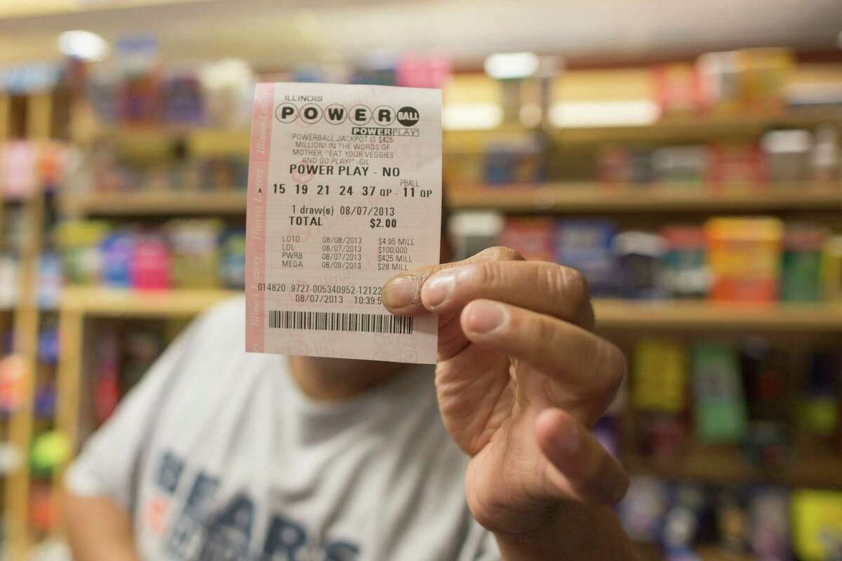 A man holds up his Powerball ticket inside of a convenience store in Chicago, Wednesday, Aug. 7, 2013. Ticketholders are hoping to win Wednesday's Powerball drawing, estimated at $425 million so far.