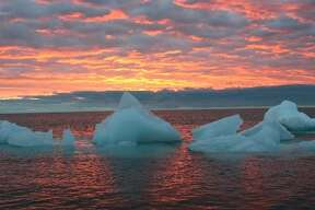 In this file photo, ice chunks float in the Arctic Ocean as the sun sets near Barrow, Alaska.