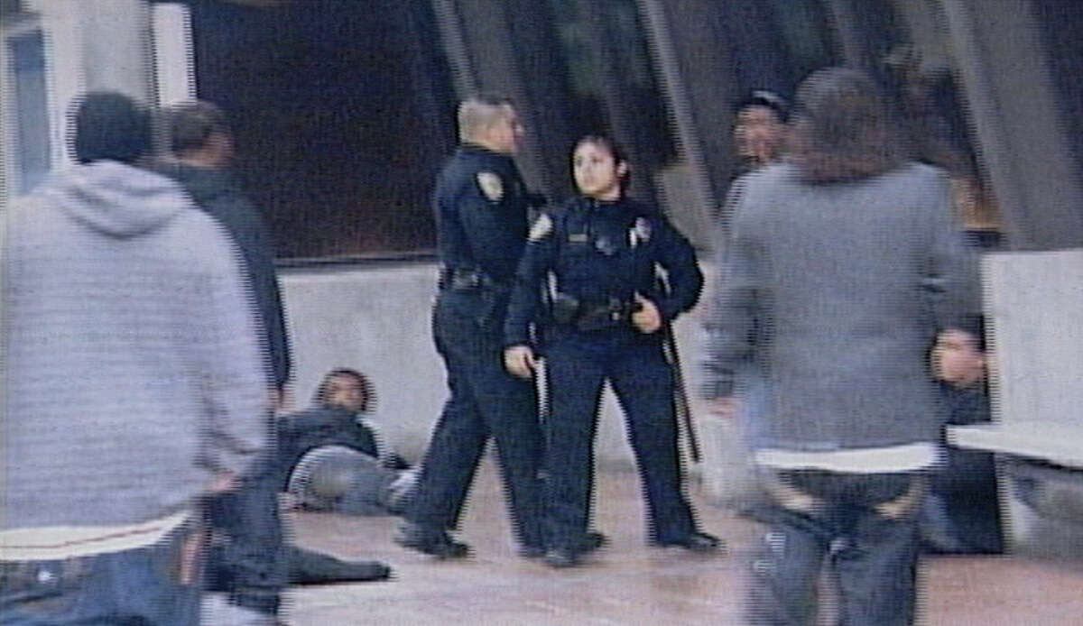 Former BART police Officer Anthony Pirone, left, moments before Oscar Grant was shot to death at the Fruitvale Station in Oakland early Jan. 1, 2009.