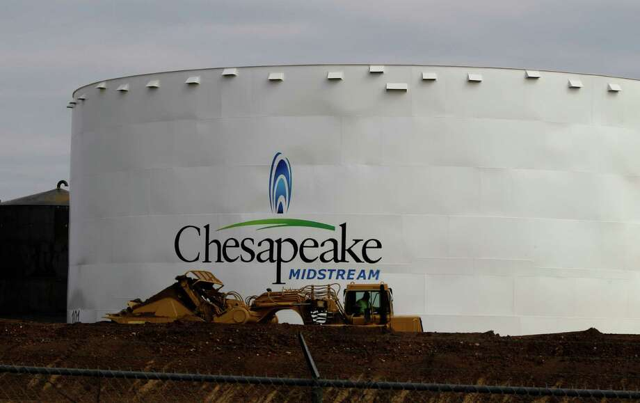 In this May 16, 2011 photo, earth-moving machinery builds up a berm around a Chesapeake Energy storage tank, near Dilley, Texas. The Oklahoma City-based company has signed a deal with a Chinese company giving them a 33 percent stake in the 600,000 acres Chesapeake has leased to extract oil and gas from TexasA'A' tightly locked Eagle Ford shale formation. (AP Photo/Pat Sullivan) Photo: Pat Sullivan / AP