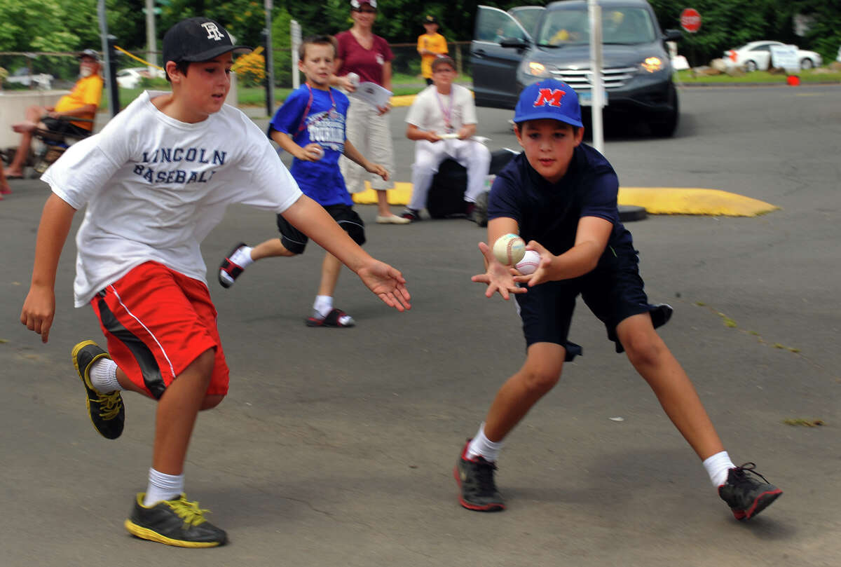 Sam Ferranti, 11, left, and his brother Alex, 10, of Lincoln, RI, chase a foul ball that flew into the parking lot during Little League Baseball Eastern Regional Tournament action between Westport and Newton South East in Bristol, Conn. on Wednesday August 7, 2013.