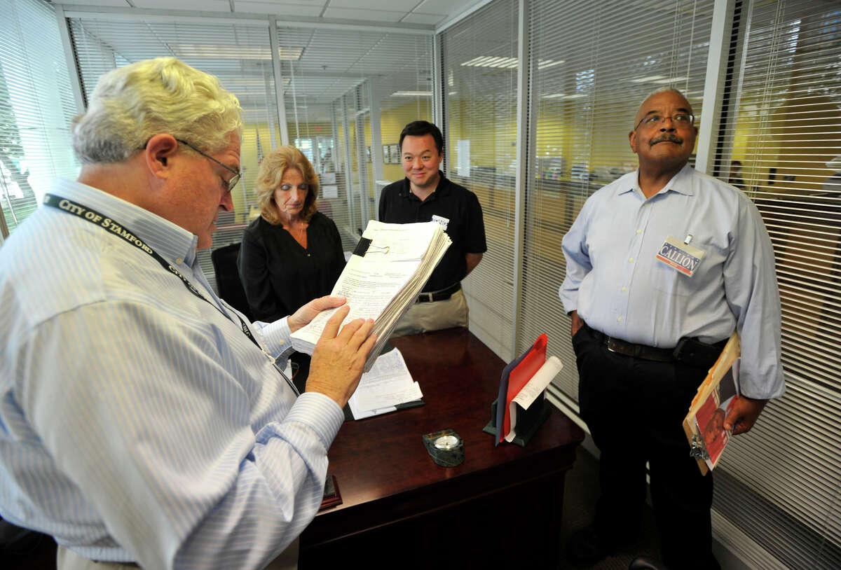 Democratic Registrar of Voters Ron Malloy, left, looks over petitions at the Stamford Government Center before handing them over to Town Clerk Donna Loglisci, second from left, as mayoral candidates State Rep. William Tong, third from left, and Bill Callion look on Wednesday, Aug. 7, 2013. Wednesday was the last day that all major party affiliated candidates were able to submit their petitions to get on the primary ballot.
