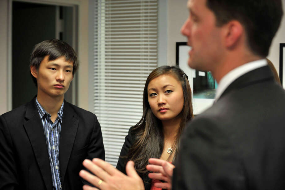 Stephen Song and his sister, Julianna, listen to Rep. Jim Himes speak during the Congressional Award ceremony reception at the congressman's office at the Stamford Government Center on Wednesday, Aug. 7, 2013. The Congressional Award recognizes people from the ages of 14 to 23 that achieve a certain number of hours in the different program areas: giving voluntary public service, working on personal development, working on physical fitness and organizing an expedition or exploring a new environment. Stephen was awarded the silver medal and Julianna was awarded the bronze medal. Photo: Jason Rearick / Stamford Advocate
