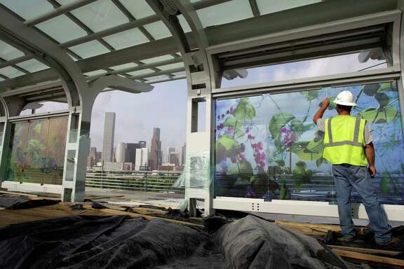Southwest Glass employee Stan Kincannon of Cleveland works on the display of artwork by Dixie Friend Gay at the Burnett Station on Metro's Northline light rail Wednesday, Aug. 7, 2013, in Houston. ( Melissa Phillip / Houston Chronicle )