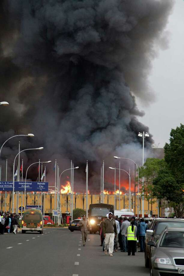 Black smoke billows from the Jomo Kenyatta International Airport in Nairobi, Kenya Wednesday, Aug. 7, 2013. The Kenya Airports Authority said the Kenya's main international airport has been closed until further notice so that emergency teams can battle the fire. (AP Photo/Sayyid Azim) ORG XMIT: AAS104 Photo: Sayyid Azim / AP
