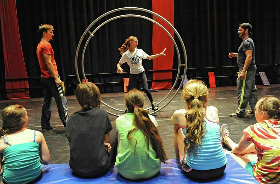 Alexa Pazienza, 13, of Clifton Park gets some help from instructors Frederick Lemieux-Cormier, left, and Nicolas Boivin, both of Montreal, on the German Wheel during Cirque Eloize circus school Monday, Aug, 5, 2013, at the GE Theatre at Proctors in Schenectady, N.Y.  (Lori Van Buren / Times Union) Photo: Lori Van Buren / 10023385A