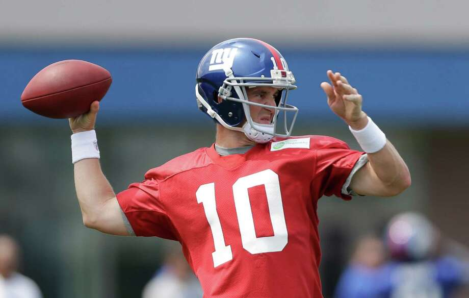 New York Giants quarterback Eli Manning throws during NFL football camp in East Rutherford, N.J., Saturday, July 27, 2013. (AP Photo/Julio Cortez) ORG XMIT: NJJC102 Photo: Julio Cortez / AP