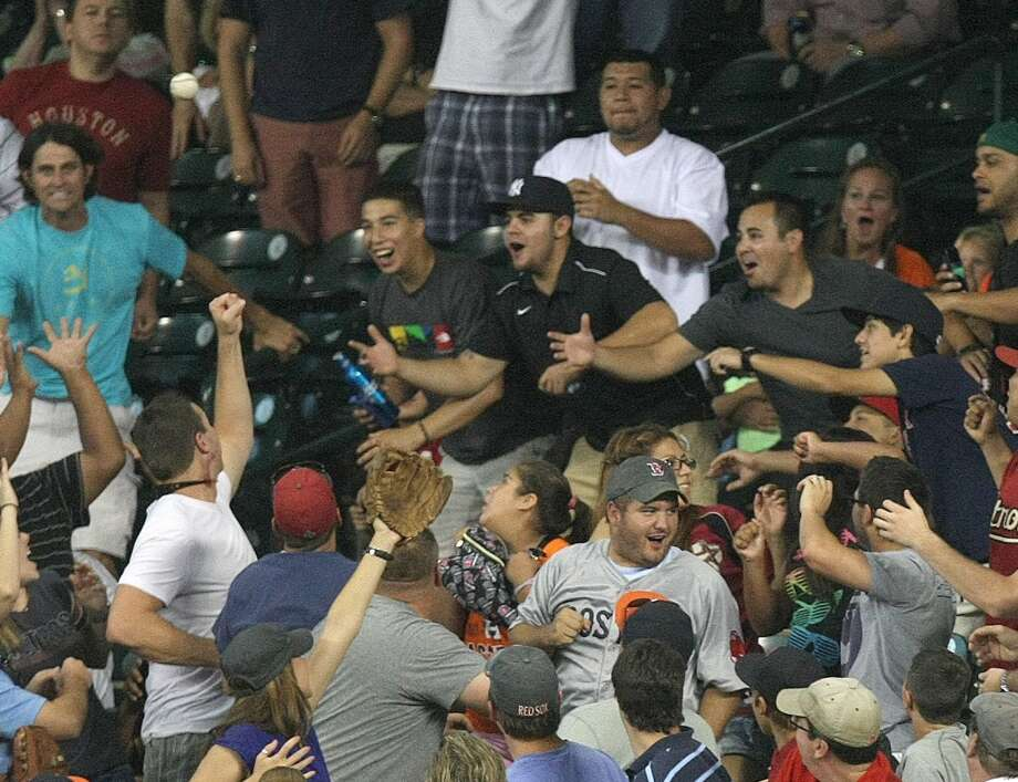 Fans in right field look to catch the two-run home run hit by Robbie Grossman. Photo: Johnny Hanson, Houston Chronicle